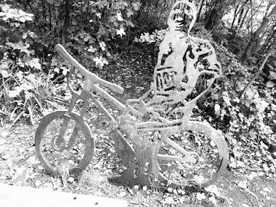Monochrome photo of a  sculpture of a man riding a bicycle. The sculpture is flat, cut from sheet metal, and stands in front of trees and bushes