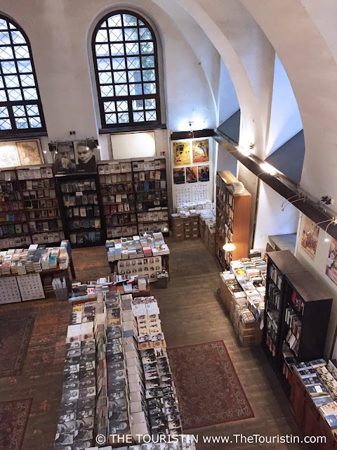 Bookshop in a vaulted hall with tables and bookshelves full of books.