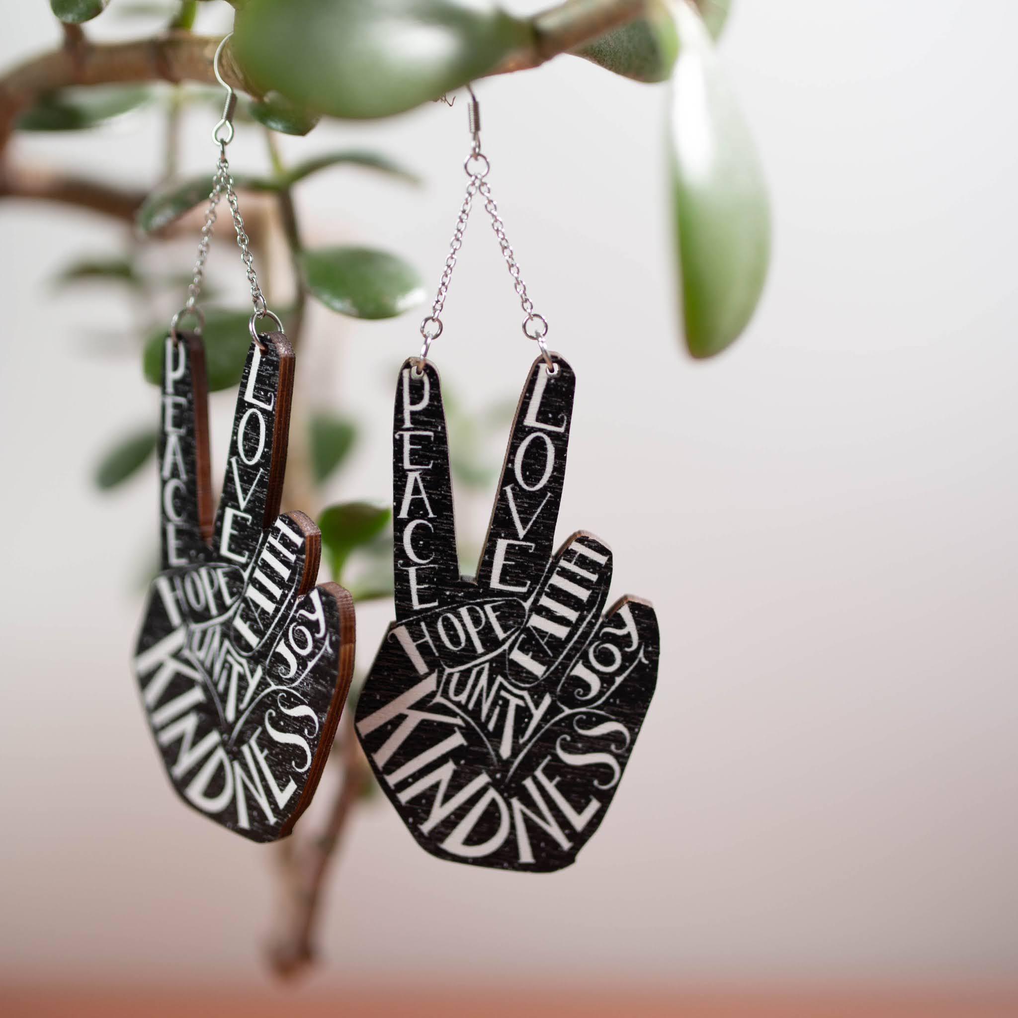 Vanerista tehdyt käsin näytetyn peace-merkin malliset korvakorut joissa on mustalla pohjalla valkeaa tekstiä.