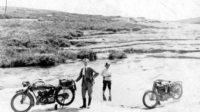 Dois jovens com suas motos próximos à beira do rio