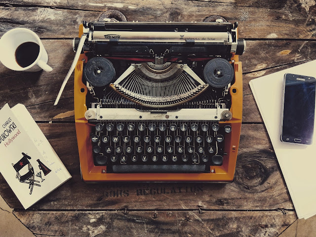 typewriter, book, coffee cup and cell phone on a table