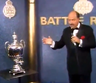 WWF / WWE: Battle Royal at the Royal Albert Hall - Mean Gene Okerlund shows off the Royal Samovar Trophy