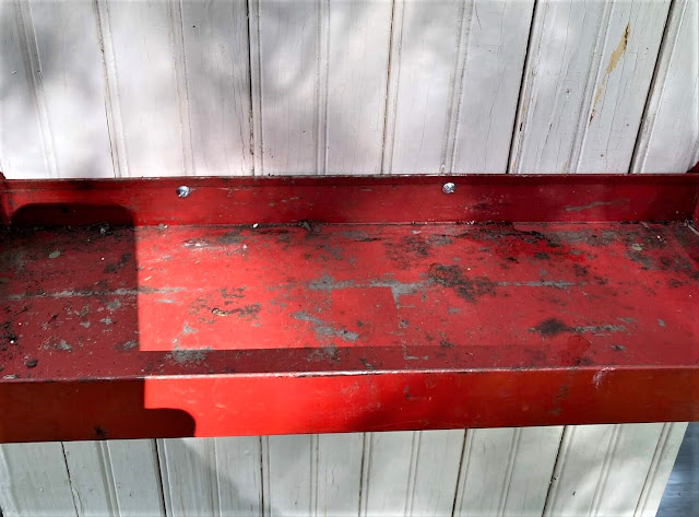 Photo of red metal garage tray screwed to a bead board cabinet door