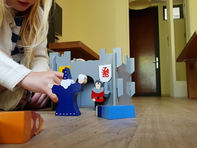 Playing with a small grey, slotted together castle on a wooden floor. Wooden character pieces are in the foreground