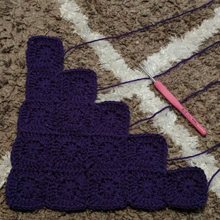 Fifteen purple crochet squares sewn together in a triangle shape.