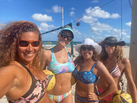 Four women on the beach in front of a beach volleyball court