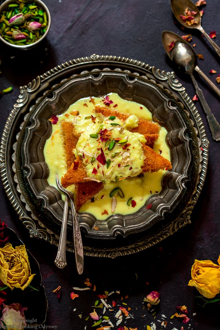 A regal dessert shahi tukda is served in a bowl with a spoon.