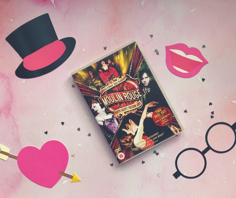 Moulin Rouge DVD sits on a pink background surrounded by small silver hearts. In the top left of the picture is a black top hat with a pink ribbon, in the bottom left is a pink heart with an arrow through it, in the top right corner is a smiling mouth, and in the bottom right is a pair of  black round spectacles.