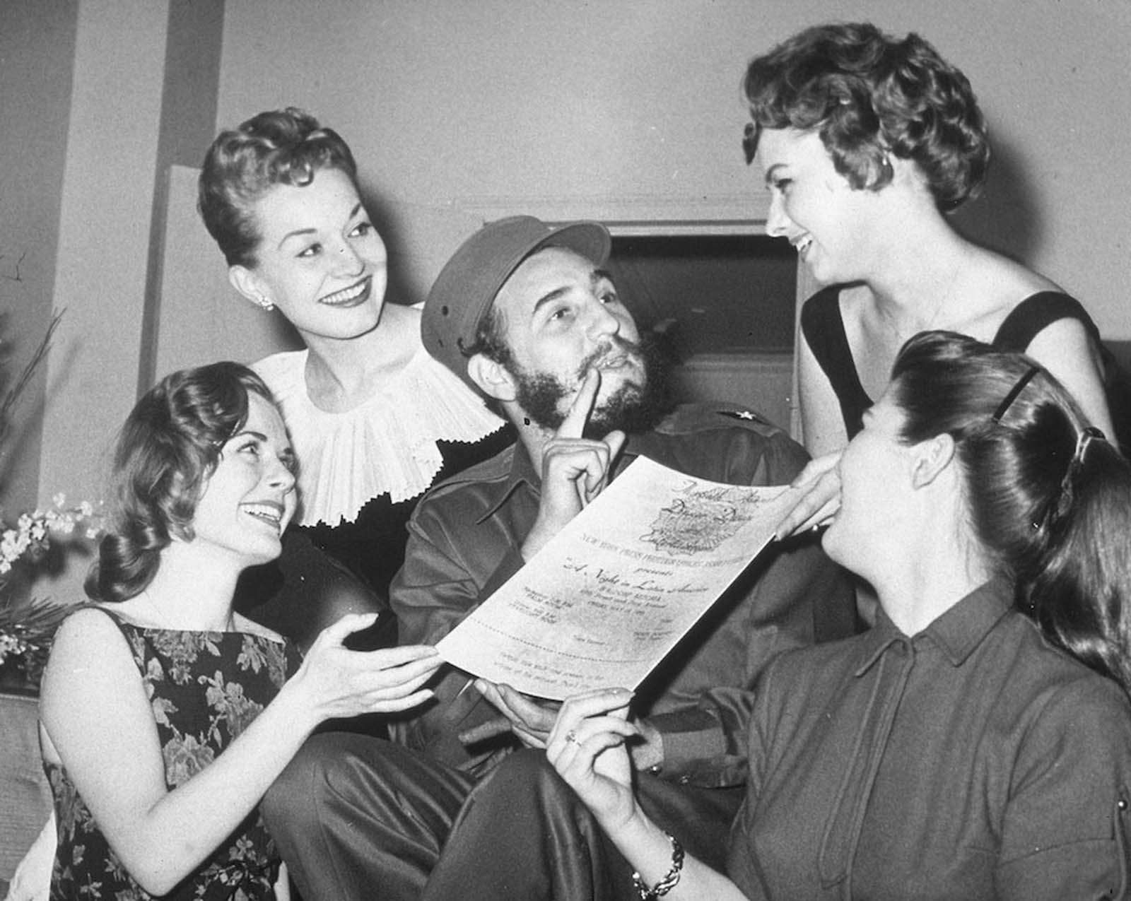 Castro is presented with an invitation to the New York Press Photographer's Ball.