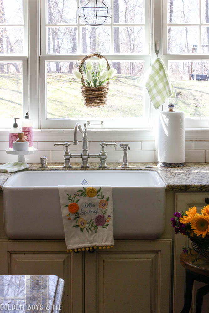 Farmhouse sink in spring kitchen with caged light pendant over sink