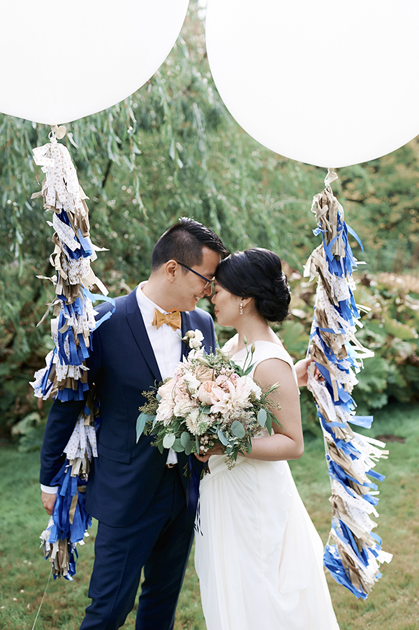 Vancouver beauty, life and style blogger Solo Lisa gets married in her hometown with a ceremony in Stanley Park and a dinner reception at Chambar. Here she poses with her husband next to two round balloons with DIY garland tassels in gold, blue, and a white-and-gold star print.