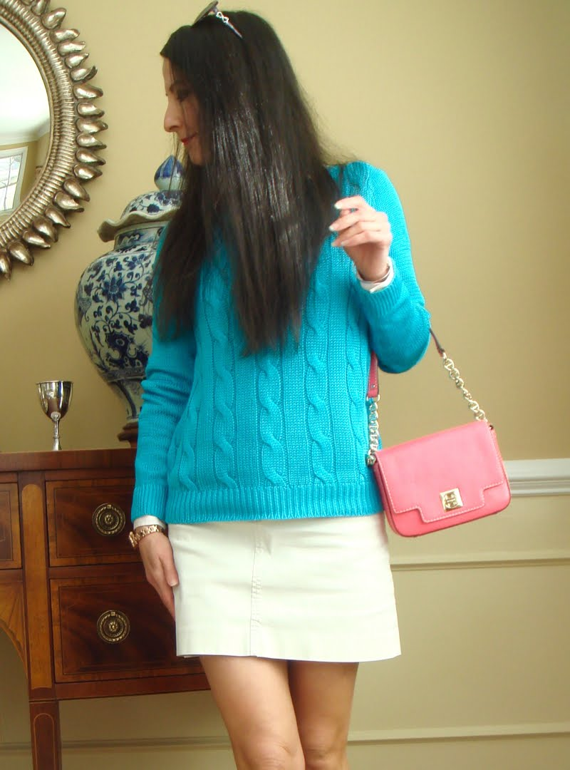 Half body shot of blue sweater and pink purse and cream mini skirt.