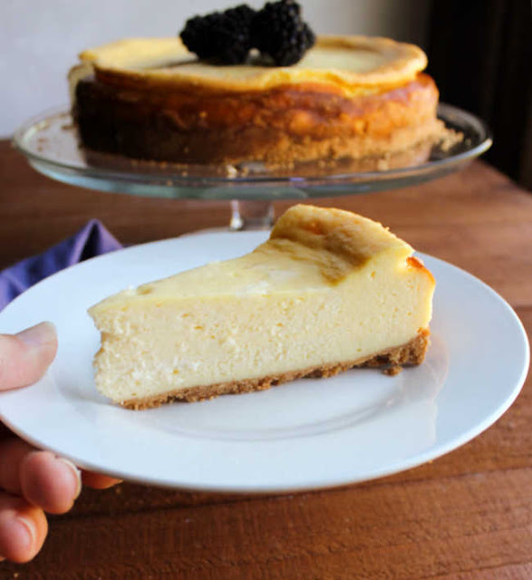 slice of cheesecake on plate with remaining cake in background