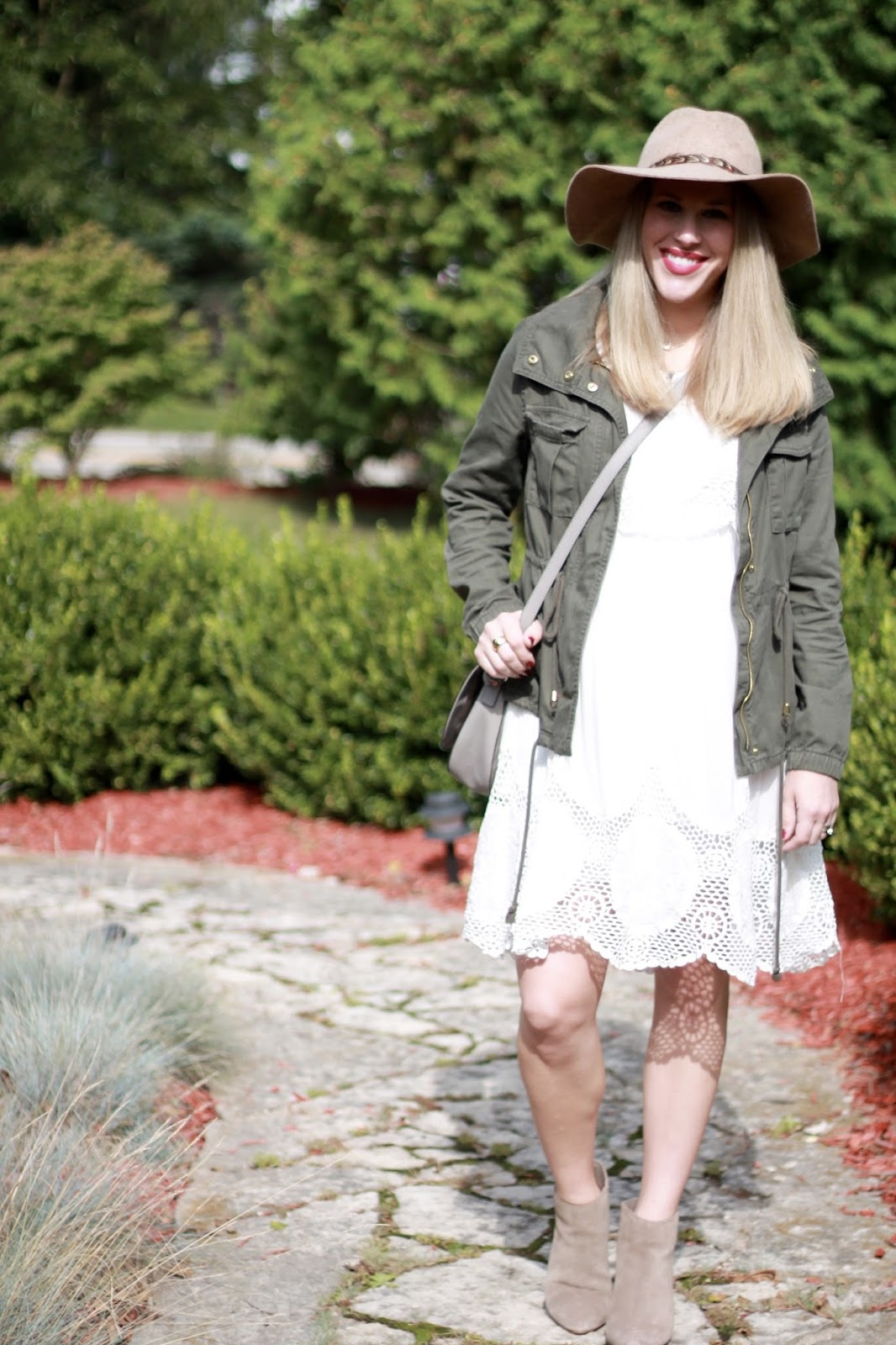 white crochet dress, olive field jacket, beige wide brim hat, taupe booties, grey saddlebag, fall maternity outfit
