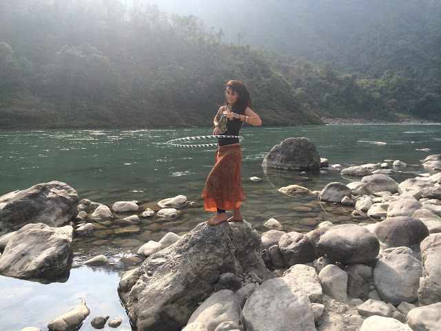 Girl using her hula hoop in the Ganges River in India.