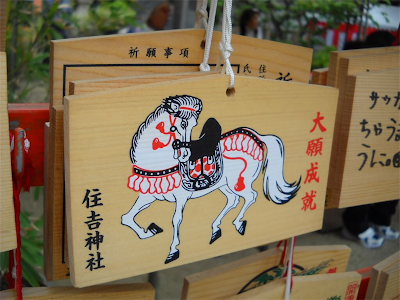 A wooden wishing plaque (ema) with a picture of a horse.