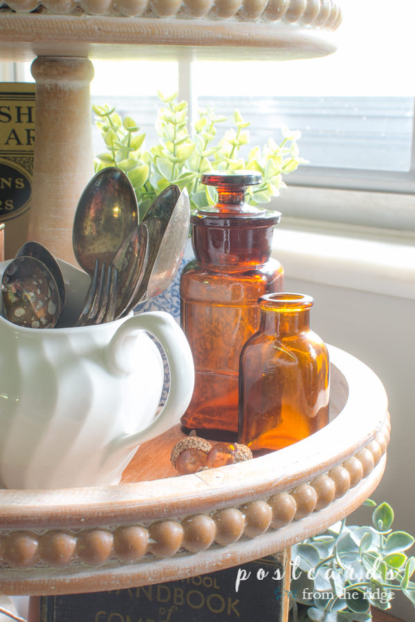 little vintage amber bottles and vintage silver in a fall tiered tray