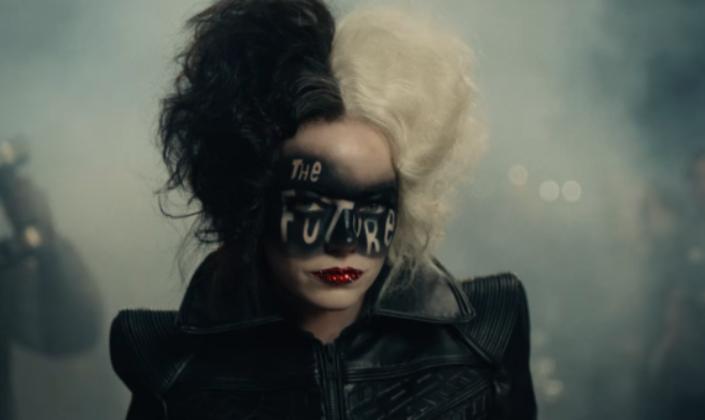 Imagem de capa: a personagem Cruella, interpretada por Emma Stone, com um casaco de couro, os cabelos pintados de preto e branco, um batom vermelho, e no rosto, acima dos olhos, uma maquiagem preta em que se lê a palavra Future escrita, por trás dela uma moto e fumaça.