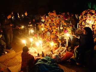 People lin candlelight gathered at a gravesite. There are flowers and skull decorations around it.