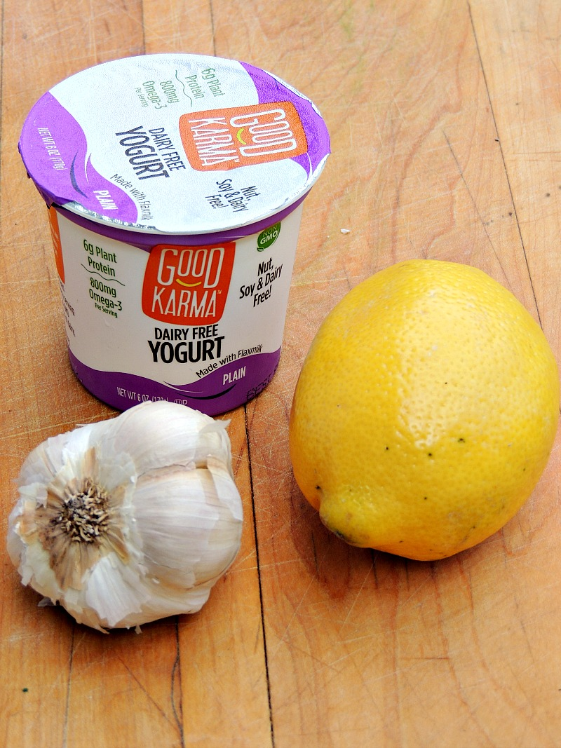 Good Karma Dairy Free Yogurt on a wooden cutting board with a lemon and a head of garlic.