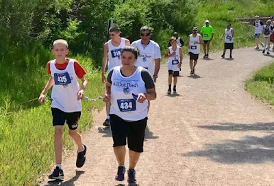 Blind and visually impaired runners, guides, and sighted runners along the Mary Carter Greenway Trail during the 1st annual NFBCO 6 Dot Dash 5K in 2018