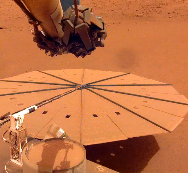 One of InSight's two large solar panels is completely covered in Martian dust...as seen by a camera on the lander's robotic arm.