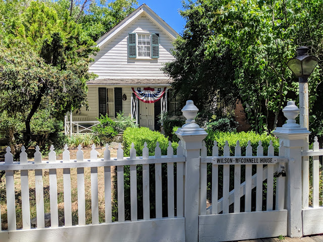 The white clapboard house sits behind a white picket fence.