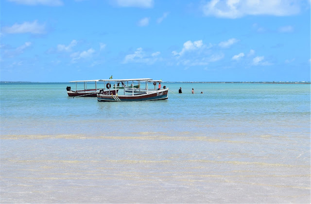 dois barcos atracando na praia