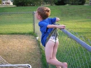 Niño salta valla y se engancha y se queda colgando