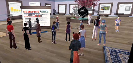 Sixteen human-looking Second Life avatars are standing in the illustrated room. Introductory information about Redefine/ABLE is on the main panel closest to tour leader, David London. Nine large wooden-framed panels with exhibition information are posted around the space.