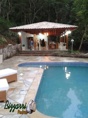 Construção de piscina de concreto revestida de azulejo com o piso de pedra São Tomé tipo cacão com a construção da churrasqueira e o muro de pedra em Atibaia-SP.