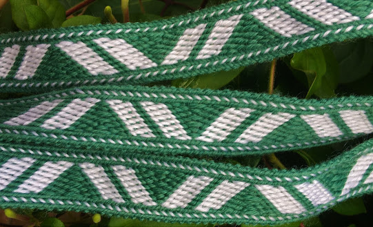 A photo of a green and white tablet woven band, placed horizontally across the frame against a leafy background and patterned with green triangles between wide white and narrow green diagonal lines