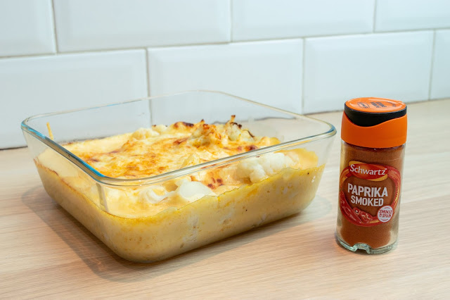 Cauliflower cheese cooked in a square glass dish and a bottle of Schwartz smoked paprika to the right.