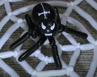 Kreuzspinne im Spinnennetz aus Luftballons geformt.
