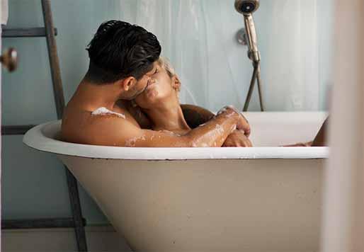 Couple in a bath tub kissing