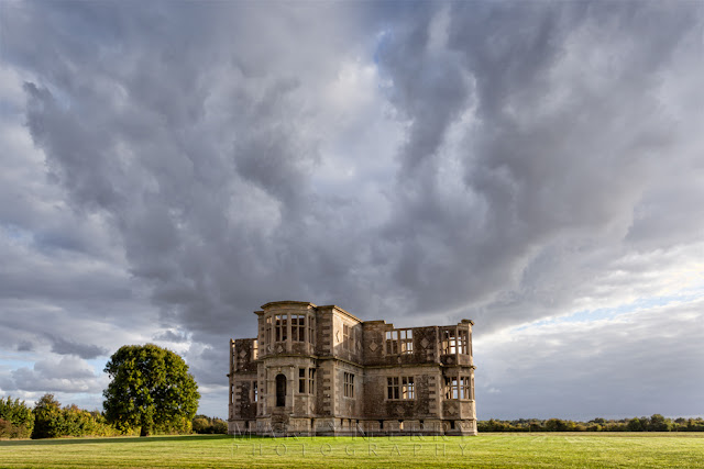 Stormy atmosphere over Lyveden New Bield as it's lit up by the evening sunshine
