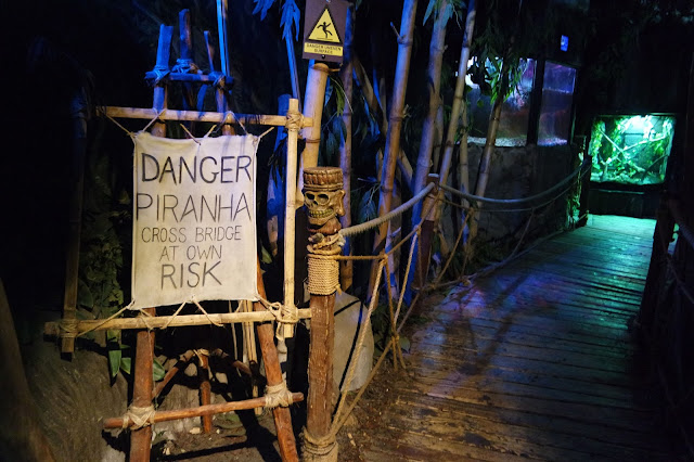 a dimly lit wooden footbridge with a rustic sign reading 'DANGER: PIRANHA cross bridge at own risk'