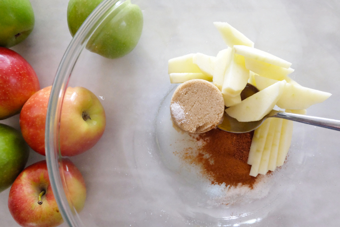 adding sliced apples to cinnamon and brown sugar