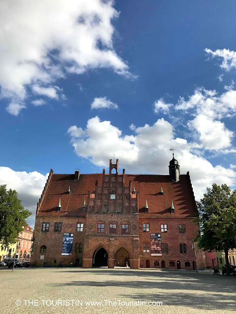 A red brick property in Gothic architecture on a cobblestone market square lined by pastel-coloured houses under a blue sky with fluffy white clouds...
