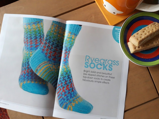 The main image of the photo is a magazine pattern picture of a pair of socks knitted in WYS Winwick Mum yarn Brightside and WYS Signature yarn Bubblegum in a mosaic pattern.  There is an orange Herdy mug and a saucer with two shortbread biscuits to the right of the picture