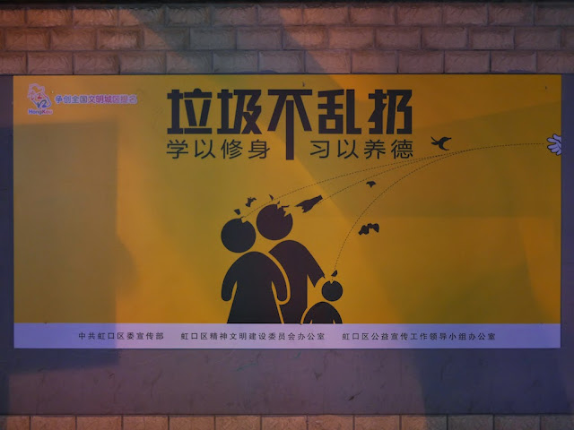 """don't litter"" (""垃圾不乱扔 学以修身 习以养德"") sign displaying objects being thrown, apparently in the direction of a family in Hongkou, Shanghai"
