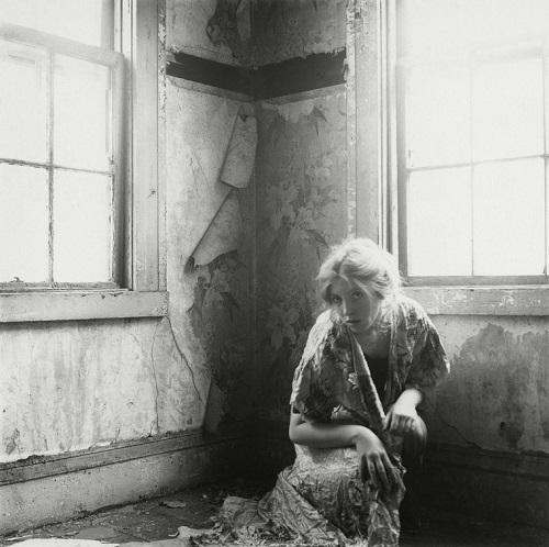 Foto artistica: una joven vestida al viejo estilo del can can posa en actitud extraña desde la esquina de una vieja habitacion.