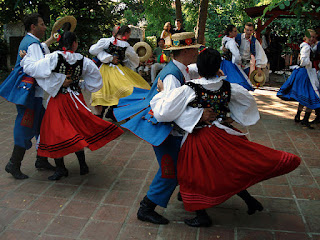A photo of folkdancers wearing traditional clothes and dancing on paving stones under trees. The women are wearing colorful skirts in red, yellow, or blue; black bodices with colorful embroidery; and white blouses with very full sleeves. The men are wearing blue trousers, long blue vests, full-sleeved white shirts, and narrow-brimmed straw hats.