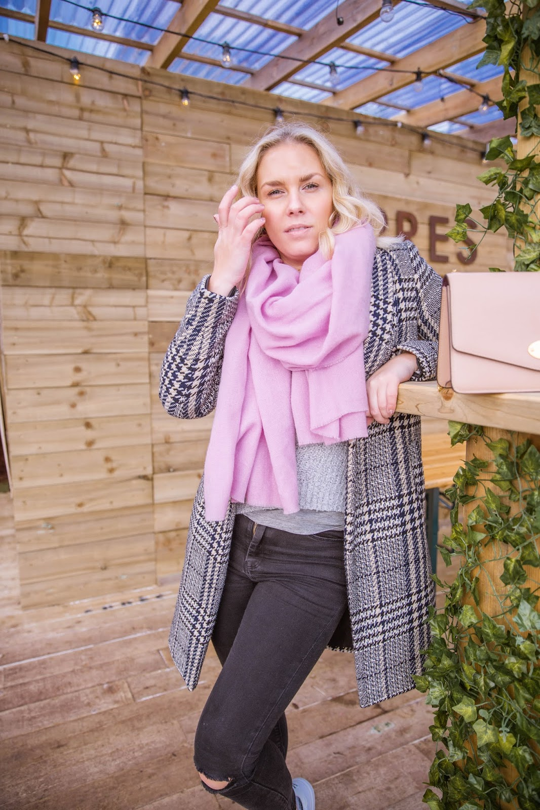 Rachel Emily posing in a wooden bar in a grey coat and pink scarf