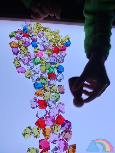 Juego libre con piedras decorativas y nins de Joguines Grapat sobre mesa de luz
