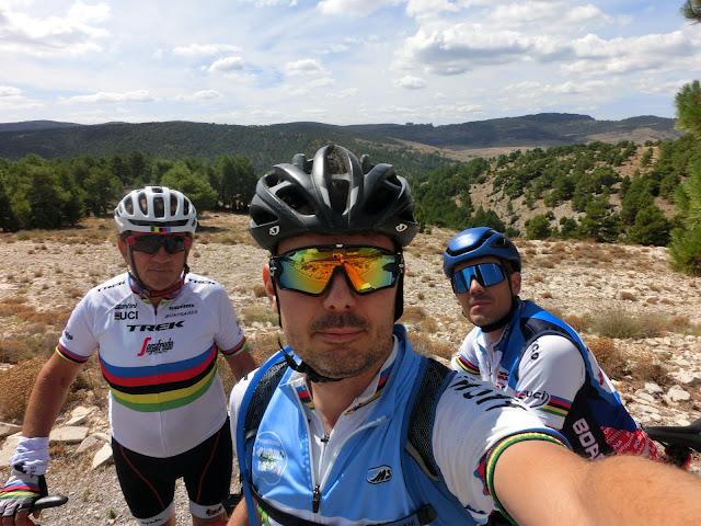tres cicloturistas con la población de puertomingalvo al fondo