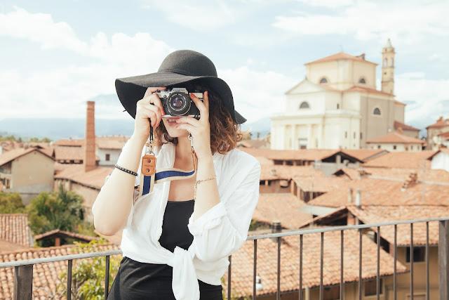 seorang wanita yang sedang memegang kamera untuk memotret