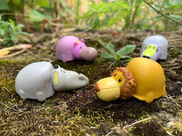 Showing lion, grey elephant, purple hippo and white tiger FlipaZoo Mini  on a mossy stone