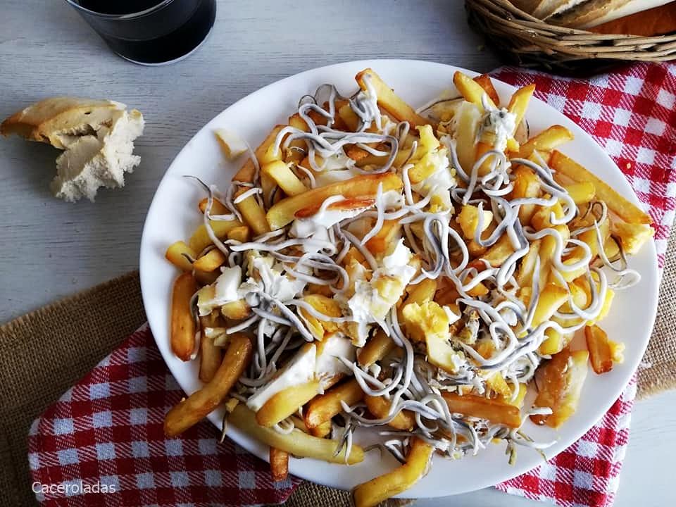 Patatas con huevos rotos y gulas al ajillo
