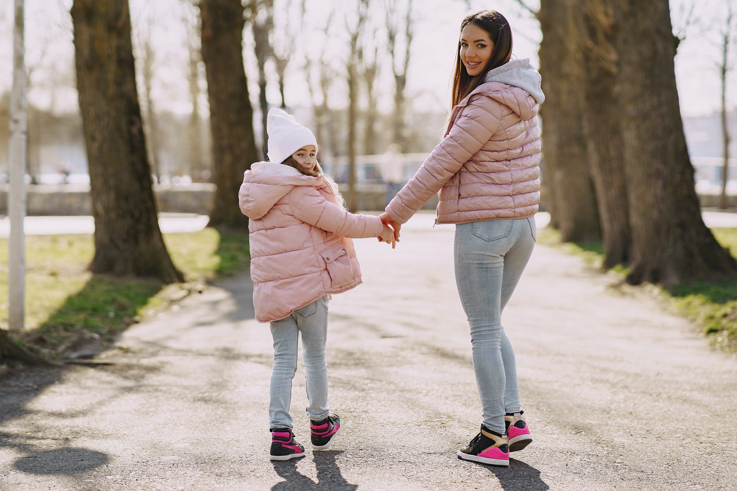 mother and daugther is similar ouftis hold each others hands and pose in the park